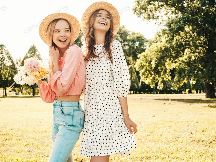 Portrait of two young beautiful women posing in the park outdoors