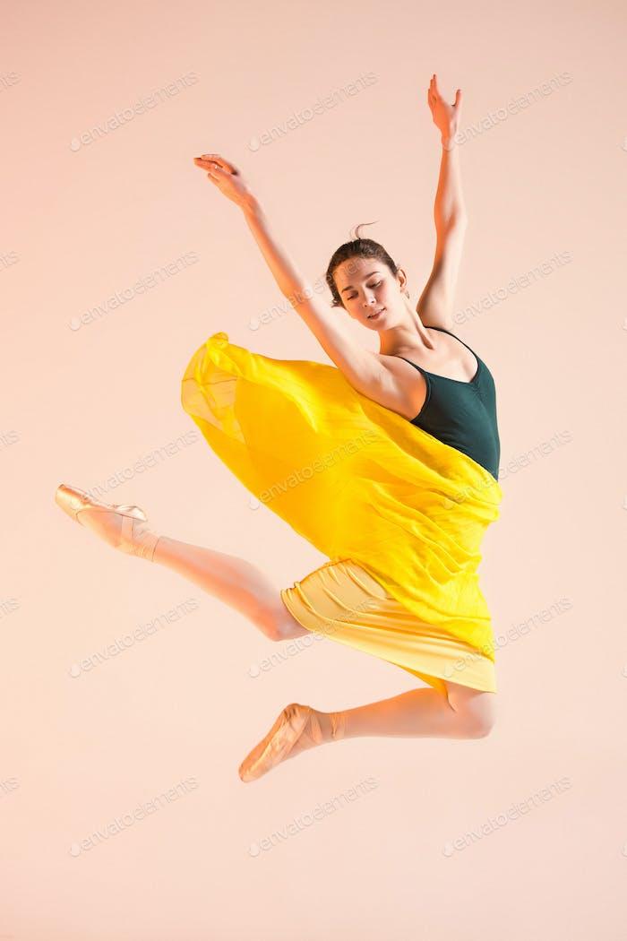 Young and incredibly beautiful ballerina is dancing at studio