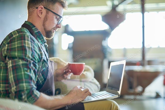 Man Using Laptop in Coffee Roastery