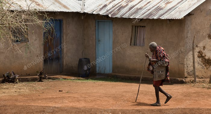Senior woman walking through village, Tanzania, Africa