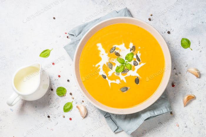 Pumpkin soup with cream at white table.