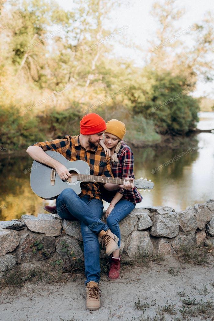 ein Kerl in einem hellen Hut spielt Gitarre mit einem Mädchen vor einem Hintergrund von Granitfelsen