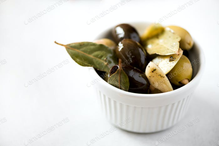 White bowl with fresh black and green olives, garlic, bay leaves on grey background. Copy space