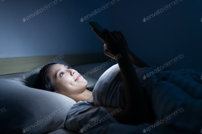 Woman use of smart phone and lying on bed