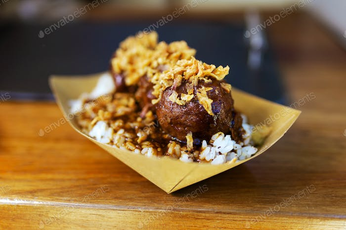 Meatballs with rice and crispy onion in a food truck.