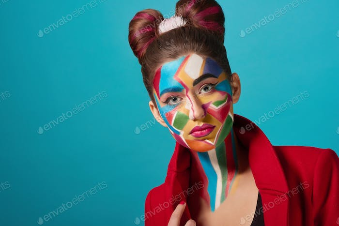 Model has bow hairstyle, funky pop art make up