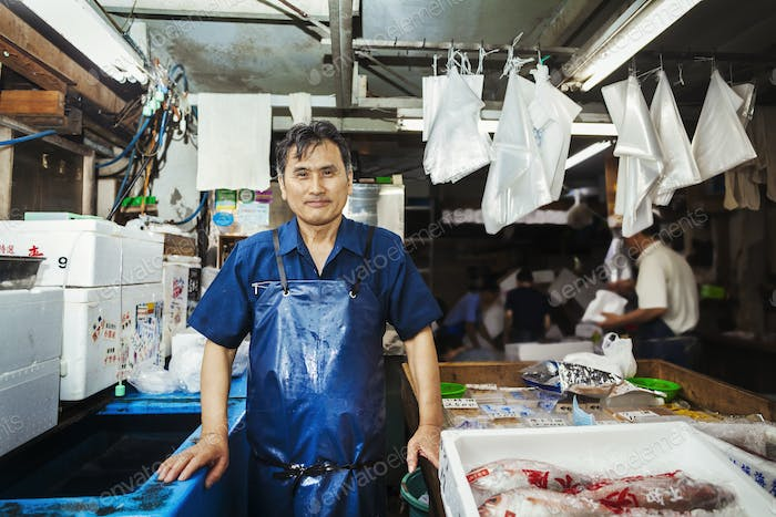 A man standing behind a stall at a traditional fresh fish market in Tokyo.