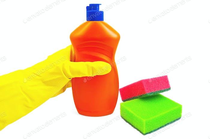 Flasche Orange mit einer gelb-handschuhten Hand und Schwämme