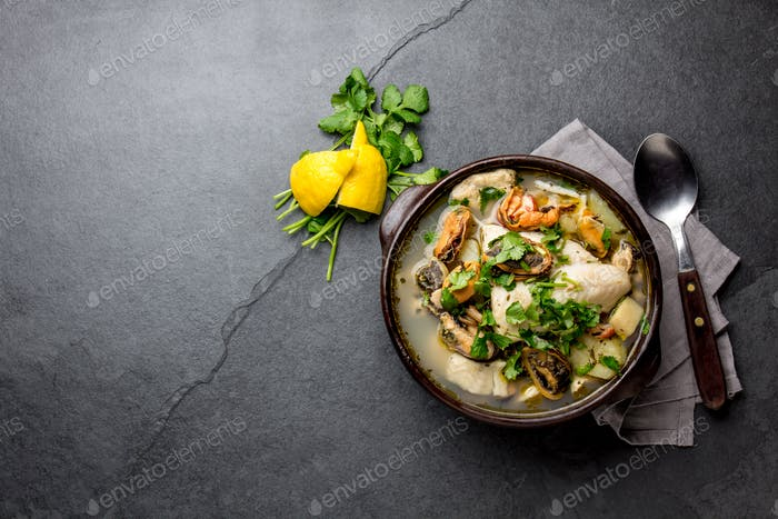 Seafood Soup in clay bowl on gray slate background