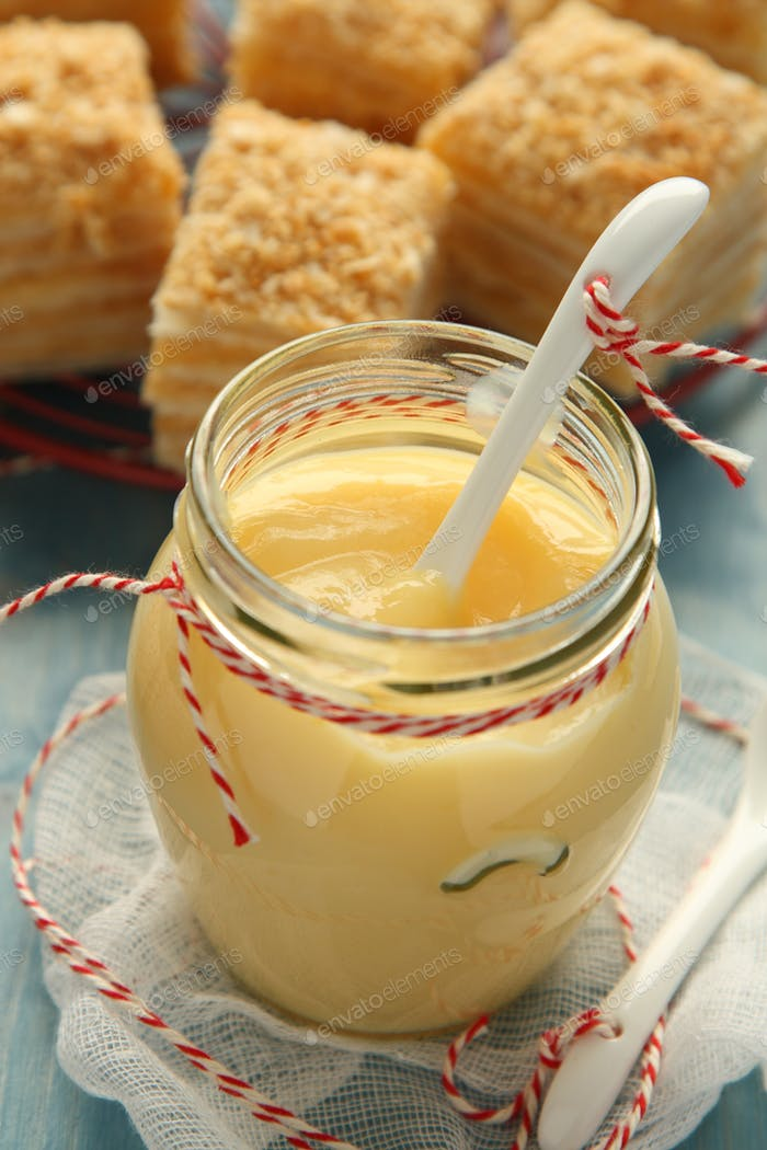 Custard cream in glass jar with white ceramic spoon