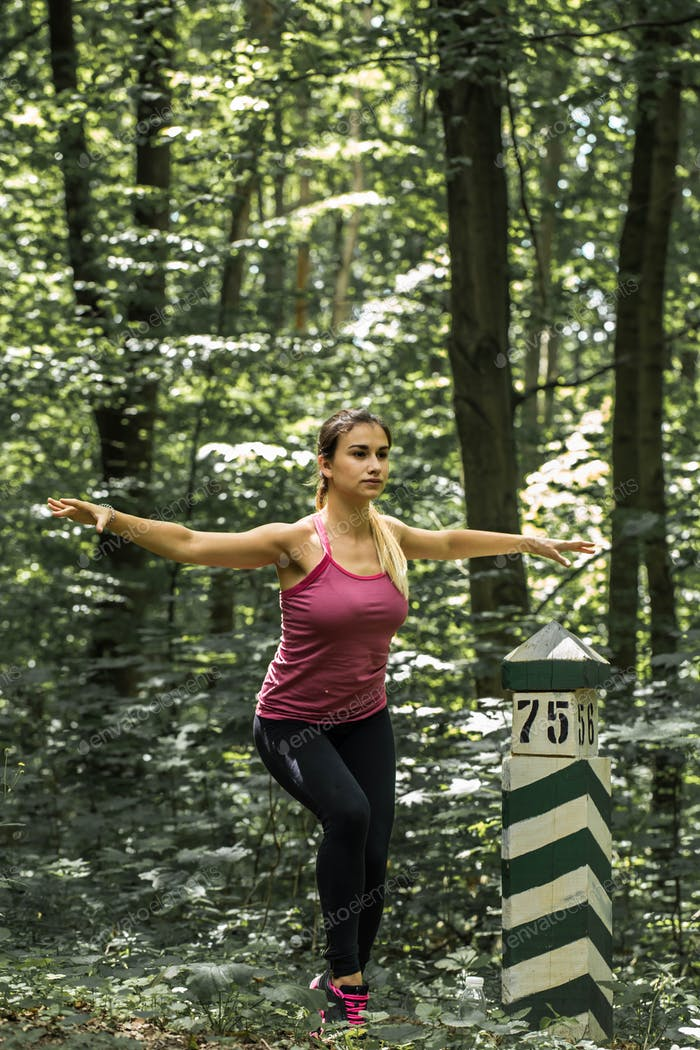 sporty girl in the woods near the index column, the warm-up before Jogging