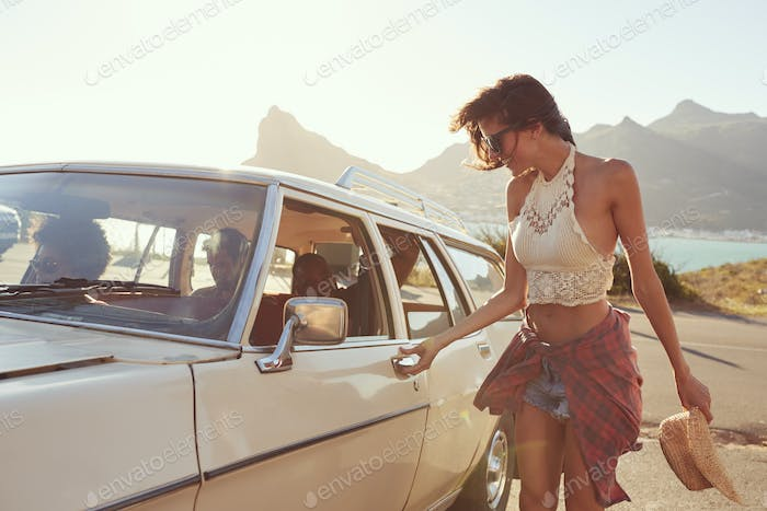 Woman Getting Into Car For Road Trip With Friends