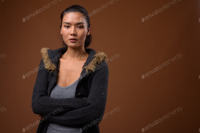 Studio shot of beautiful Asian woman against brown background
