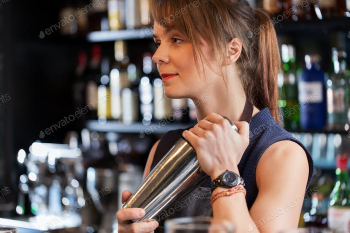 barmaid with shaker preparing cocktail at bar