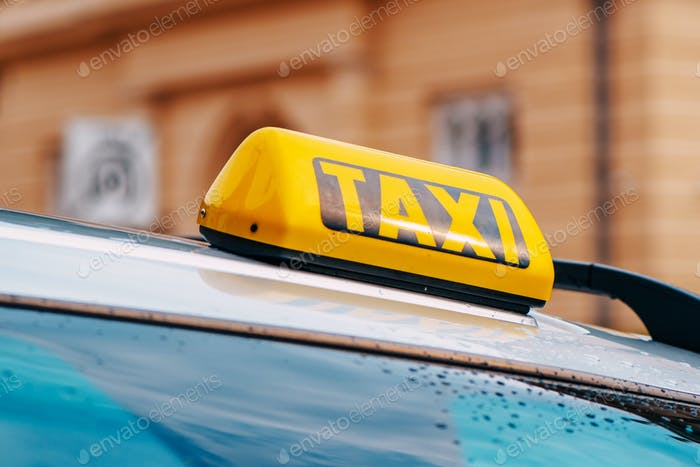 Yellow taxi sign on car roof
