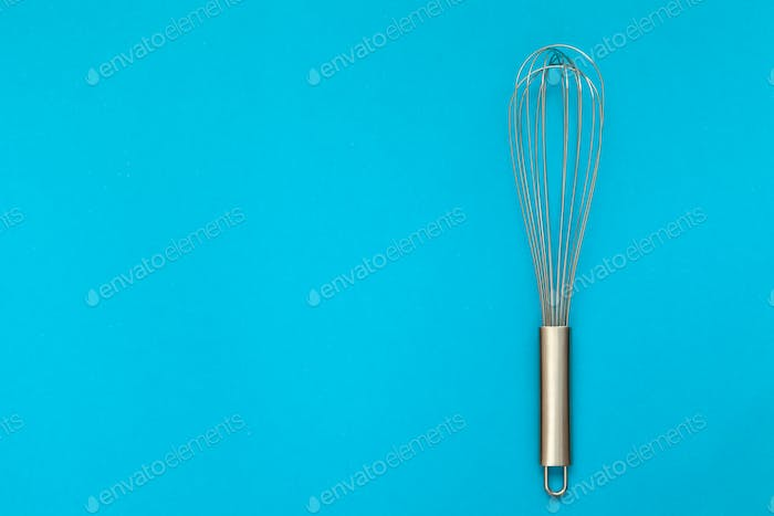 Metal whisk for whipping on a blue background