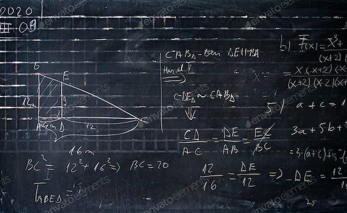 Mathematische Formeln geschrieben von weißer Kreide auf dem Tafelhintergrund.