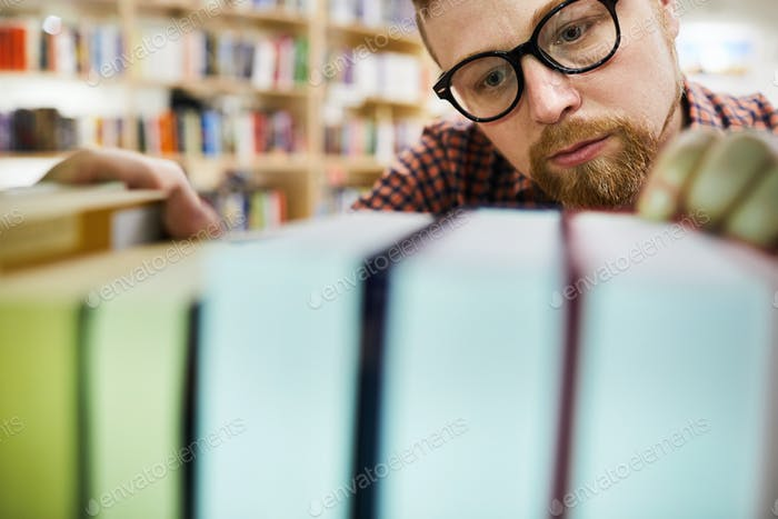 Concentrated librarian finding book