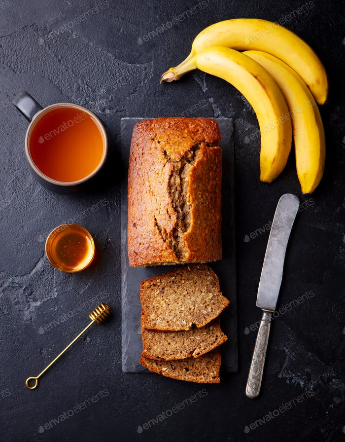 Banana, Coconut Bread, Cake with Cup of Tea on Slate Board. Dark Stone Background. Top View.
