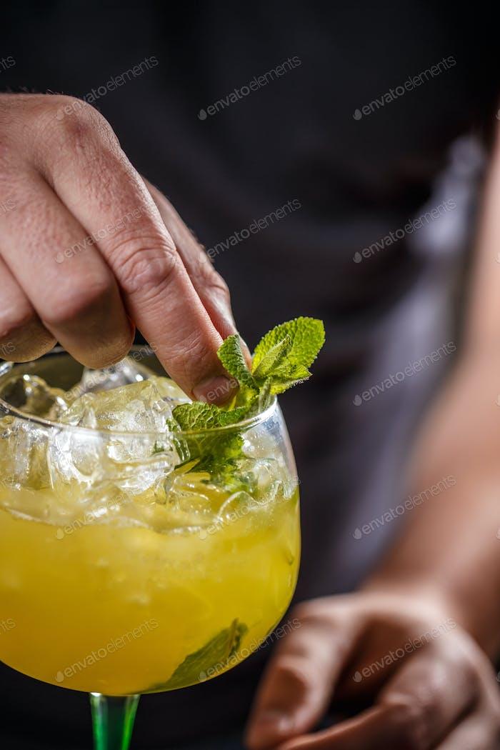Barman schmückt Cocktail