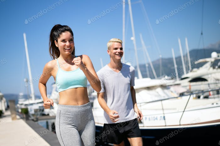 Couple running. Happy people jogging on beach, working out smiling happy