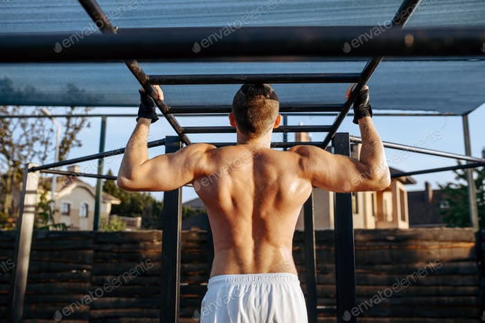 Man does pull-ups on horizontal bar, workout