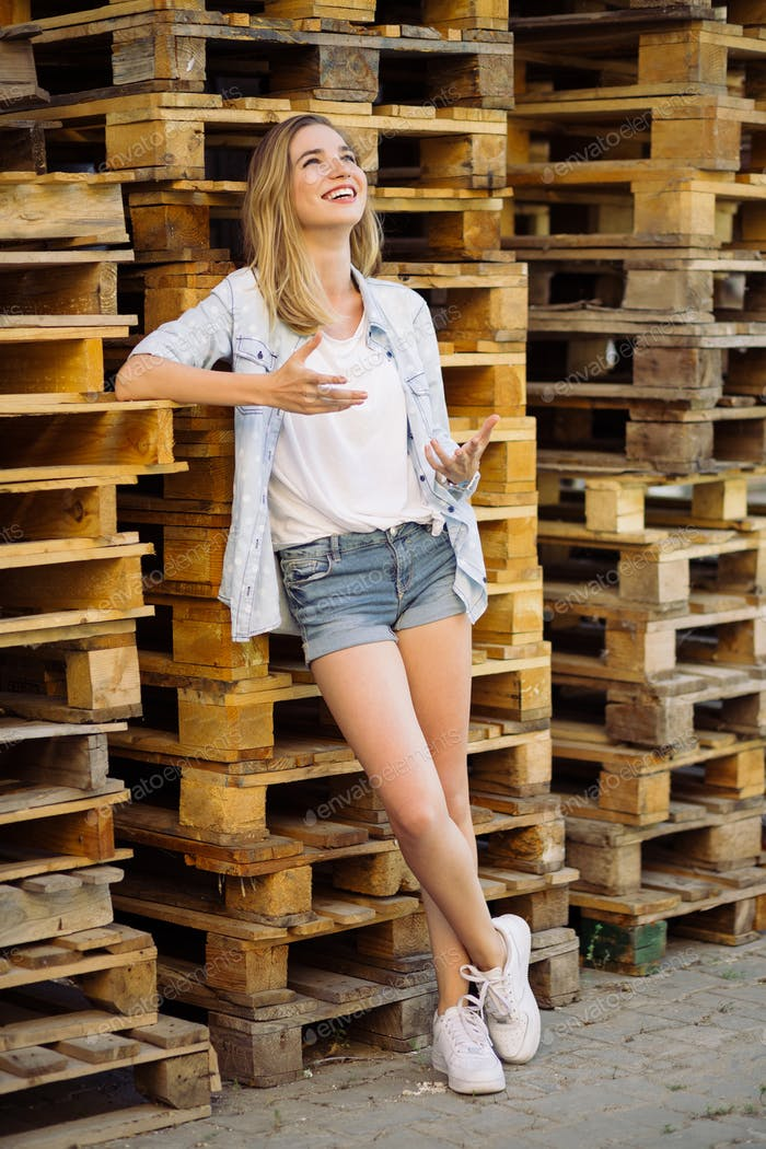 Charming girl standing near pallets