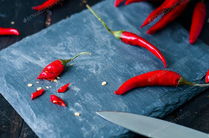 Slicing Chilli pepper with Knife on kitchen board
