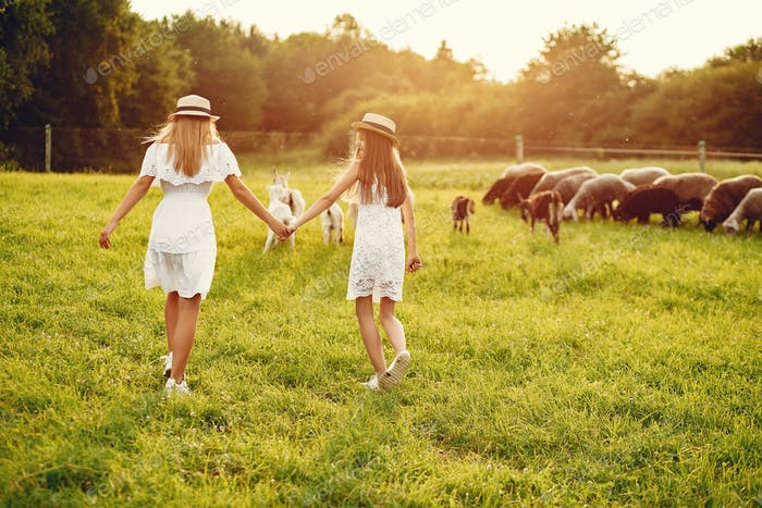 Two cute girls in a field with a goats