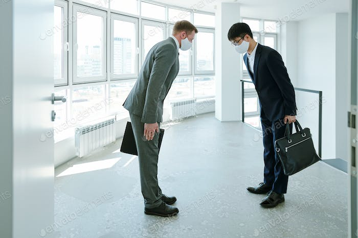 Elegant intercultural businessmen with briefcases greeting each other by bow