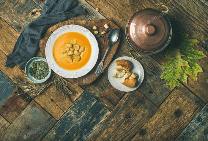 Fall pumpkin cream soup with croutons and seeds, top view
