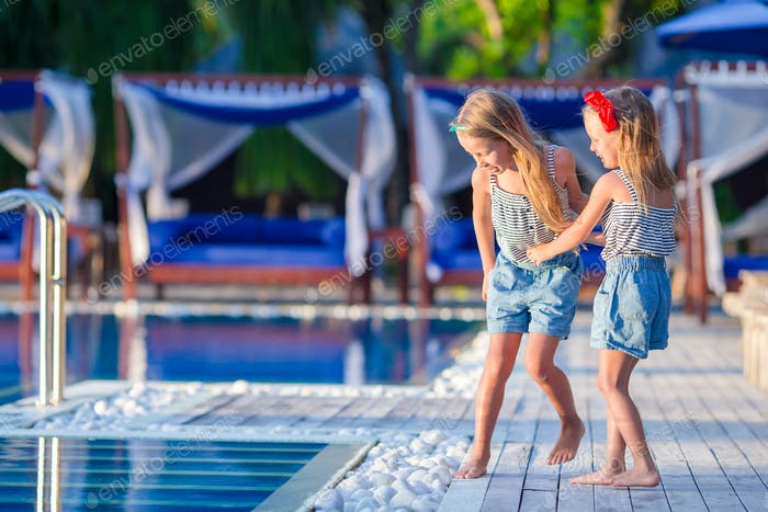 Adorable little girls at luxuxry resort during summer vacation