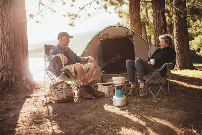 Couple relaxing on chairs by tent at campsite