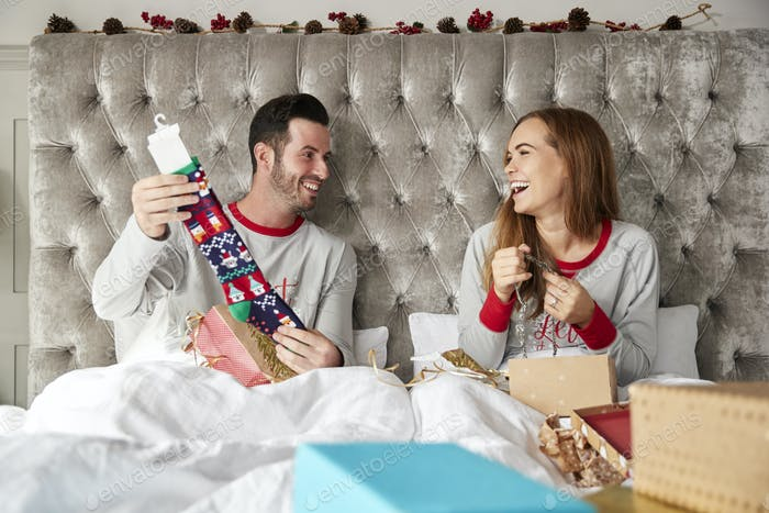 Front View Of Couple In Bed At Home Opening Gifts On Christmas Day