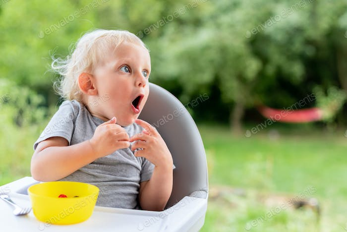 Surprised baby child looking at something while eating outdoor