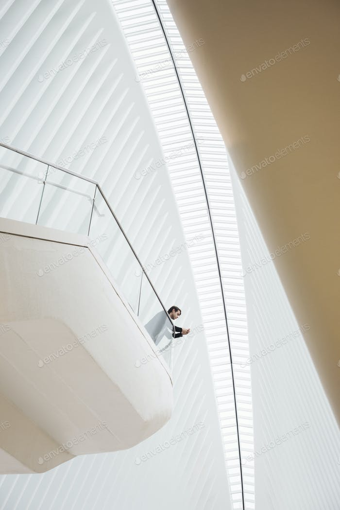 View from below of a man standing on a balcony in the Oculus building on his phone, leaning on the