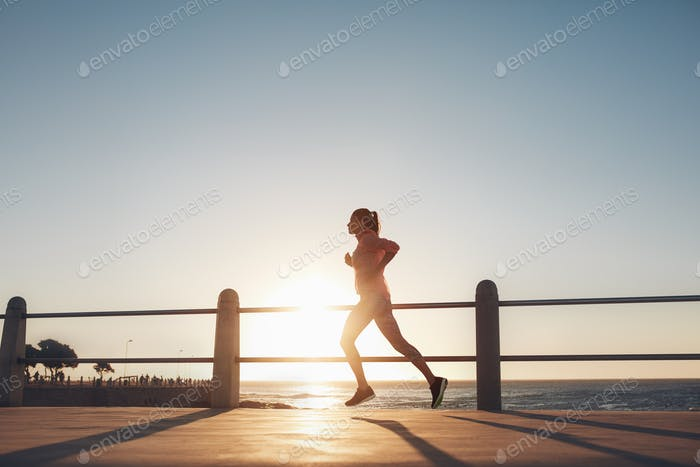 Young woman running along the sea during sunset