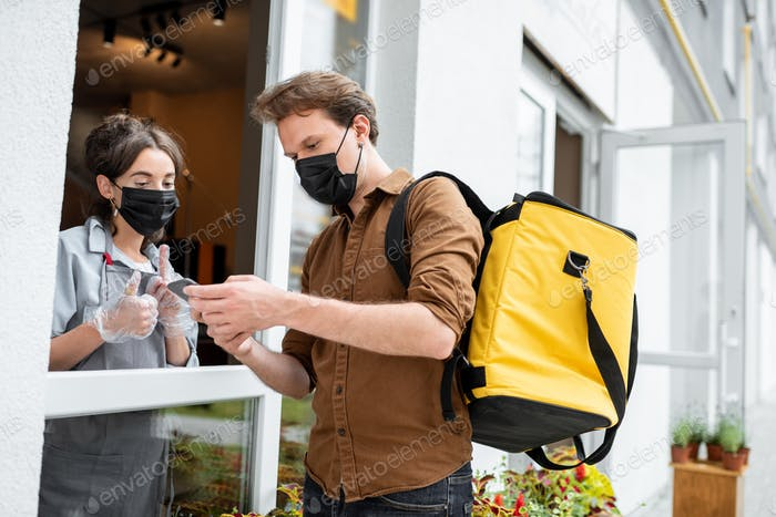 Kurier nimmt eine Bestellung für die Lieferung aus dem Schaufenster