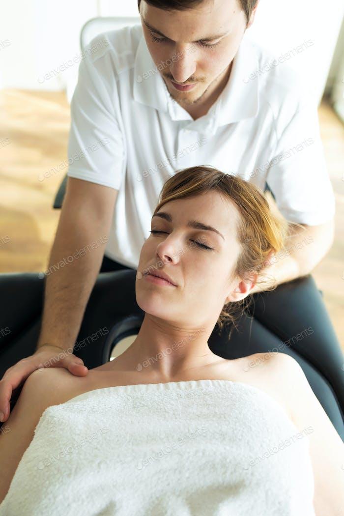 Junger Physiotherapeut, der dem Patienten eine Nackenbehandlung in einem Physiotherapieraum macht.
