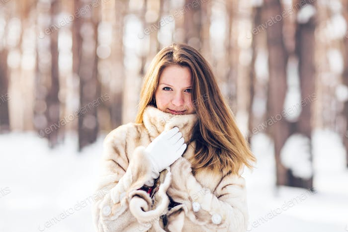 Winter portrait of young beautiful woman wearing fur coat. Snow winter beauty fashion concept.