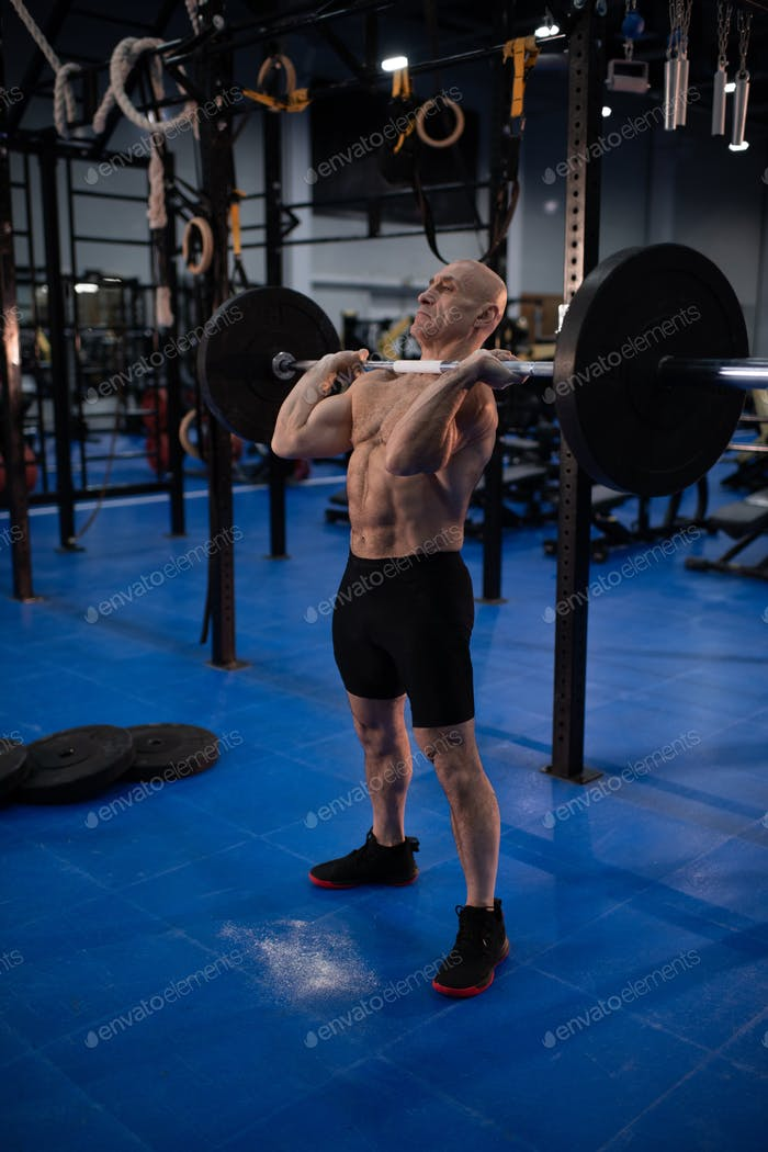 Muscular senior man with barbell in gym