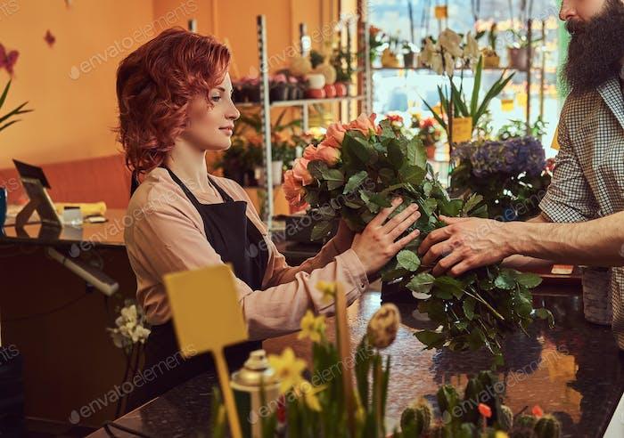 Hombre barbudo compra ramo de flores en la tienda de flores.