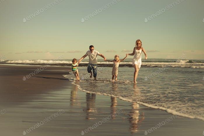 Glückliche Familie zu Fuß am Strand am Tag Zeit.