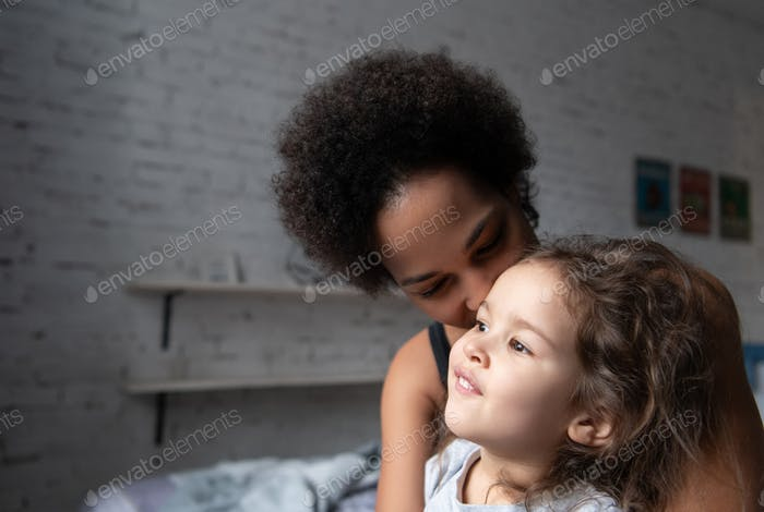 Ethnic mother hugging daughter at home