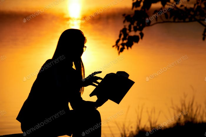 Silhouette of woman reading book