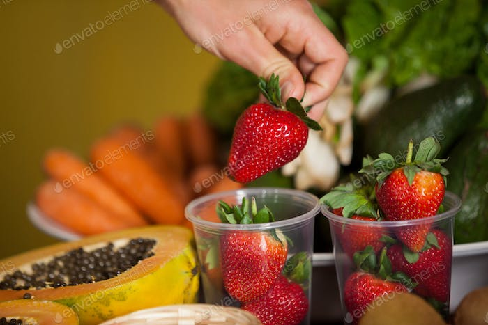 Hand of male staff holding strawberry