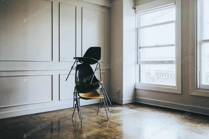Stacked chairs in an empty room
