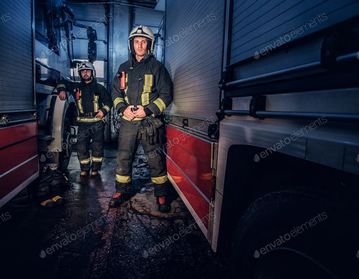 Full-length portrait of two brave firemen in protective uniform