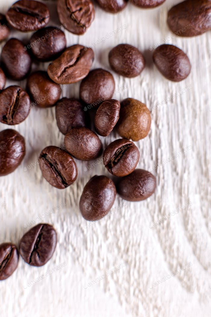 Coffee beans or grain on white wooden background. Flat lay.