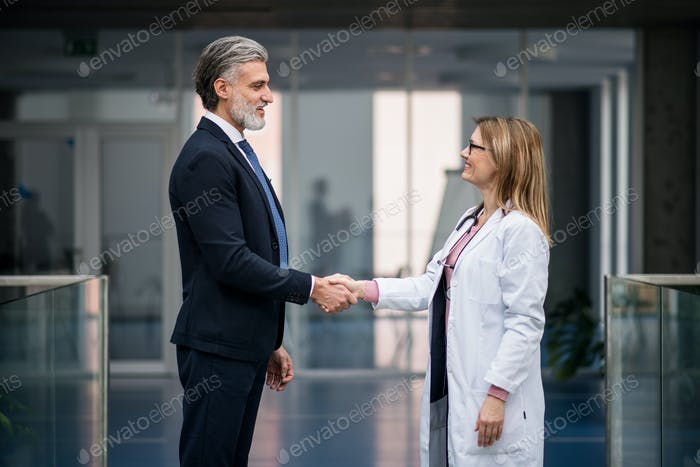 Doctor talking to pharmaceutical sales representative, shaking hands